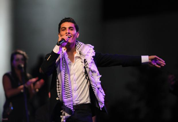 """Palestinian winner of """"Arab Idol"""" Mohammed Assaf  performs in the West Bank city of Ramallah  on July 1, 2013. Mohammed Assaf, 22, the Gaza singer who won the prestigious Arab Idol talent contest, holds the celebration concert in Ramallah as part of a three-day West Bank tour. AFP PHOTO/ABBAS MOMANI        (Photo credit should read ABBAS MOMANI/AFP/Getty Images)"""