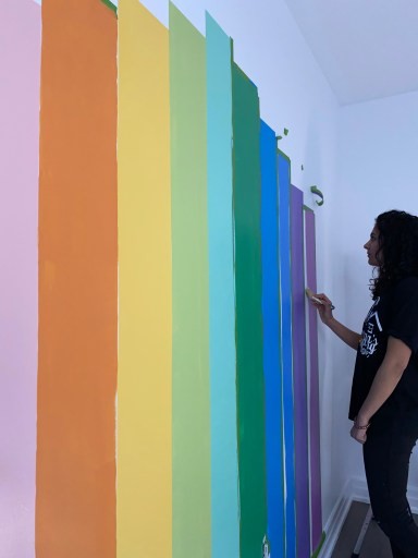 The finishing touches on the rainbow mural take the longest. Retaping the stripes to get a crisp line