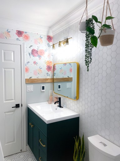 hanging planters in a girls bathroom with a floral wallpaper and hexagon wall tiles