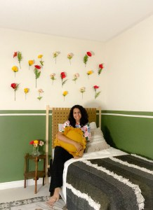 Green half accent wall with flowers on the wall