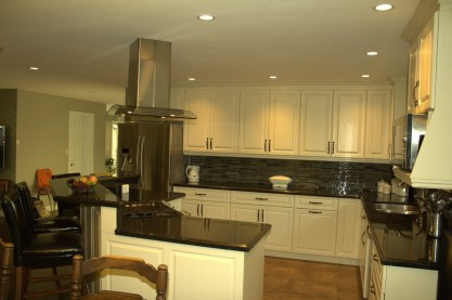 Off white painted cabinets, raised panel doors, dark countertops, and stainless steel appliances make for a gorgeous combination in a kitchen.