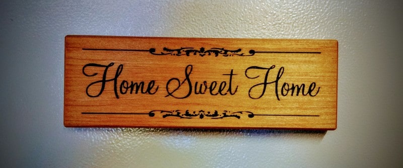 Front view of a small engraved wooden quote reads home sweet home. Magnetic