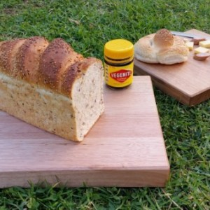 chopping boards on green grass with a loaf of bread and vegemite spread kabana and cheese with knife