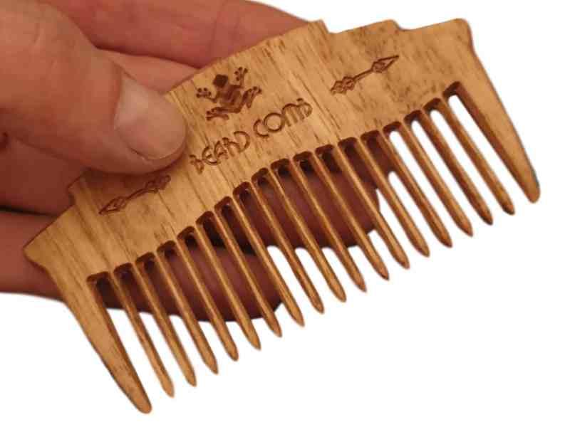 wooden beard comb in hand