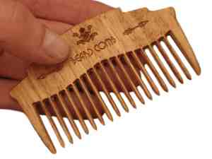 wooden beard comb in hand