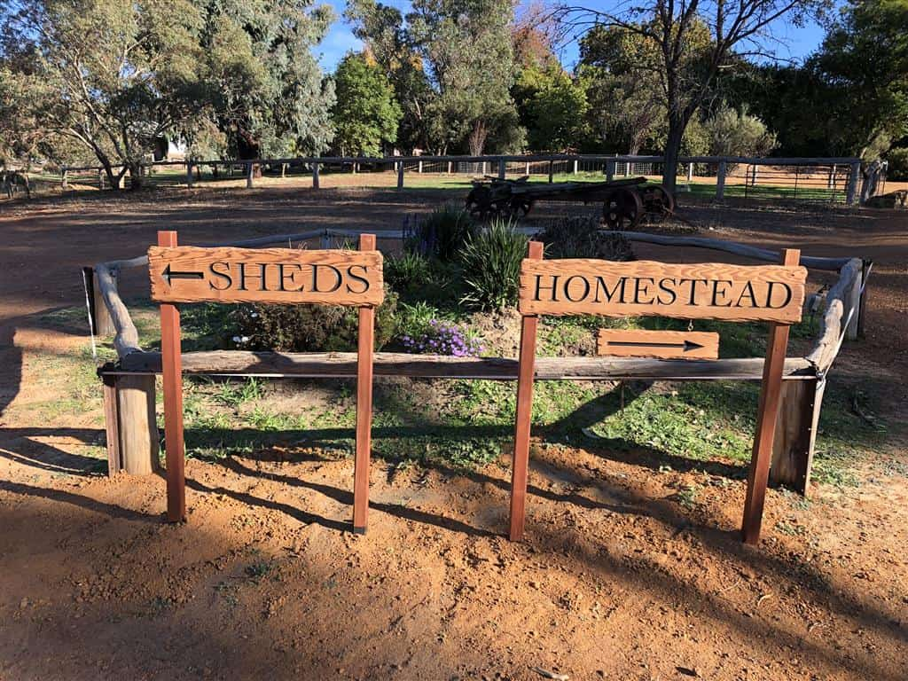 An example of some directional signs made from Cedar with rustic edges and arrows directing customers in a car park with a country setting scene behind. SHEDS pointing left and HOMESTEAD pointing right
