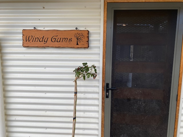 cedar sign at front door - windy gums with tree swept over