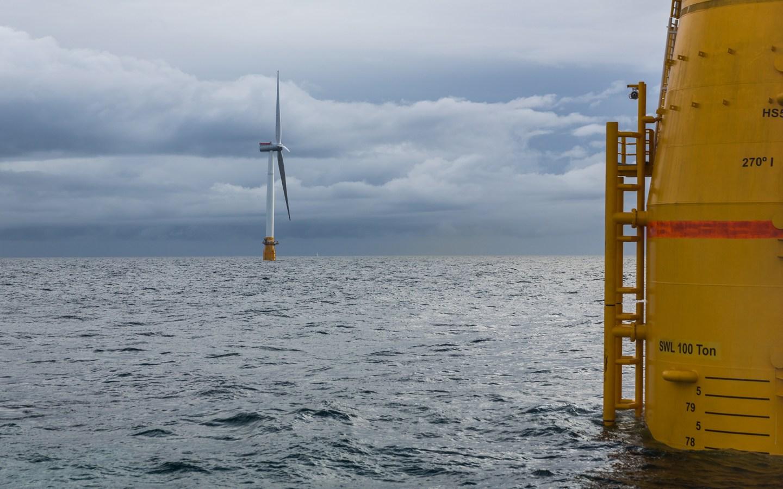 Offshore vindturbin ved siden av oljeplattform. Foto