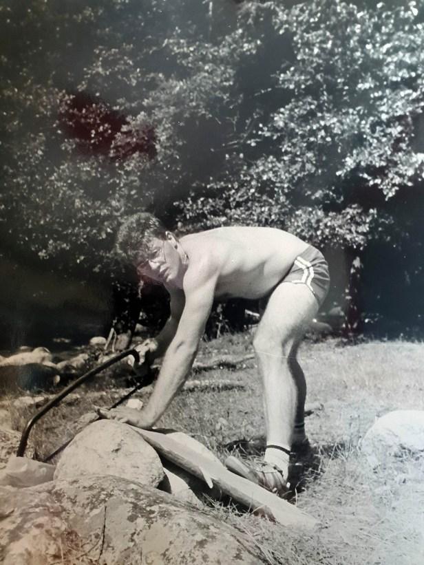 Photo en noir et blanc de Thierry VAN DEN BIL lors d'un Camp Eclaireurs en 1987, à Montpezat sous Bauzon, en Ardèche. Il est en train de scier une buche. La photo a la moitié gauche jaunie.
