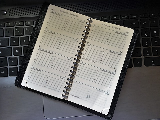 Un agenda papier ouvert posé sur un clavier d'ordinateur