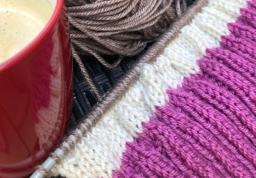 knitting with pink ribbed collar