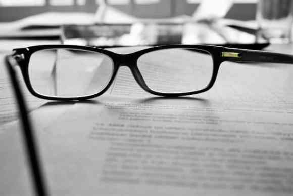 Pair of glasses resting on proofreading sheets, or are they editing sheets?