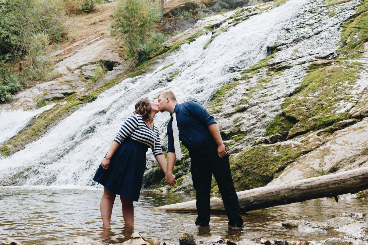 couple kissing in front of waterfall, colville, washington