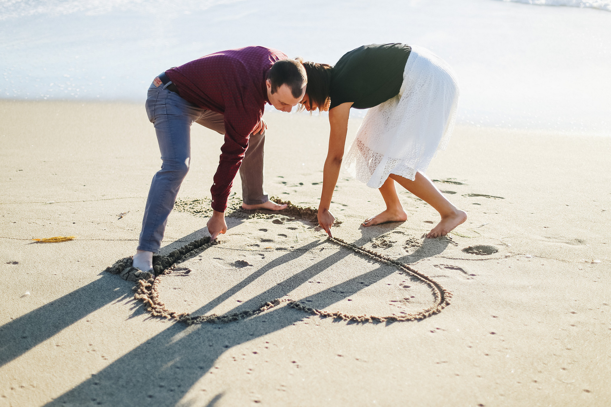 drawing hearts in the sand -- engagement photos on point dume state beach in california