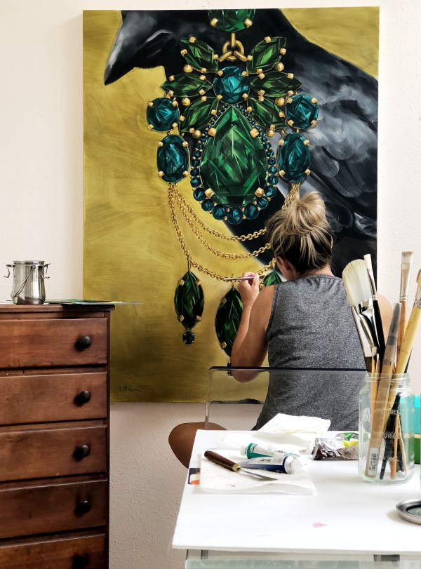 studio view of Dallas, Texas artist Hannah Brownlarge painting a scale oil painting of a crow wearing an oversized emerald and tourmaline earring