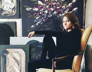 Dallas, Texas artist Hannah Brown sitting sideways in a chair posing with a cluster of her artwork behind her