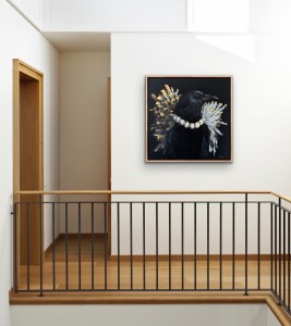 bold and dramatic oil painting of a black crow wearing a diamond necklace with a black background painted by Dallas, Texas artist Hannah Brown displayed in an elegant and modern room
