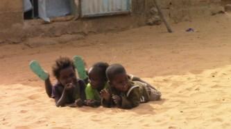 Little siblings rolling in the dirt