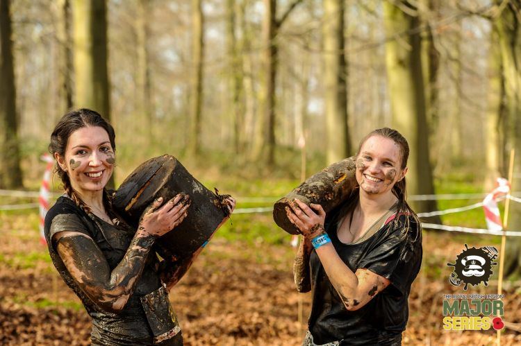 Girls carrying logs in woods