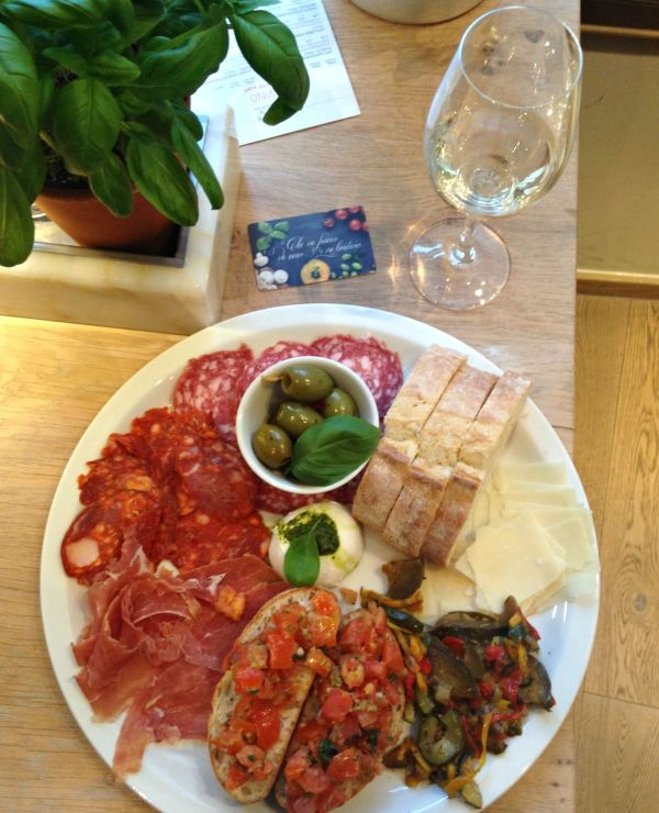 grande antipasti starter at vapiano on table with glass of wine