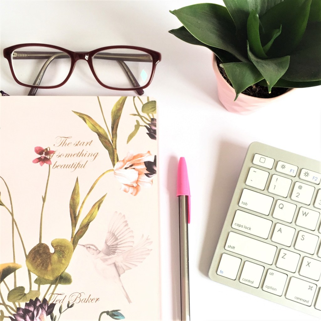 notebook glasses and plant flat lay
