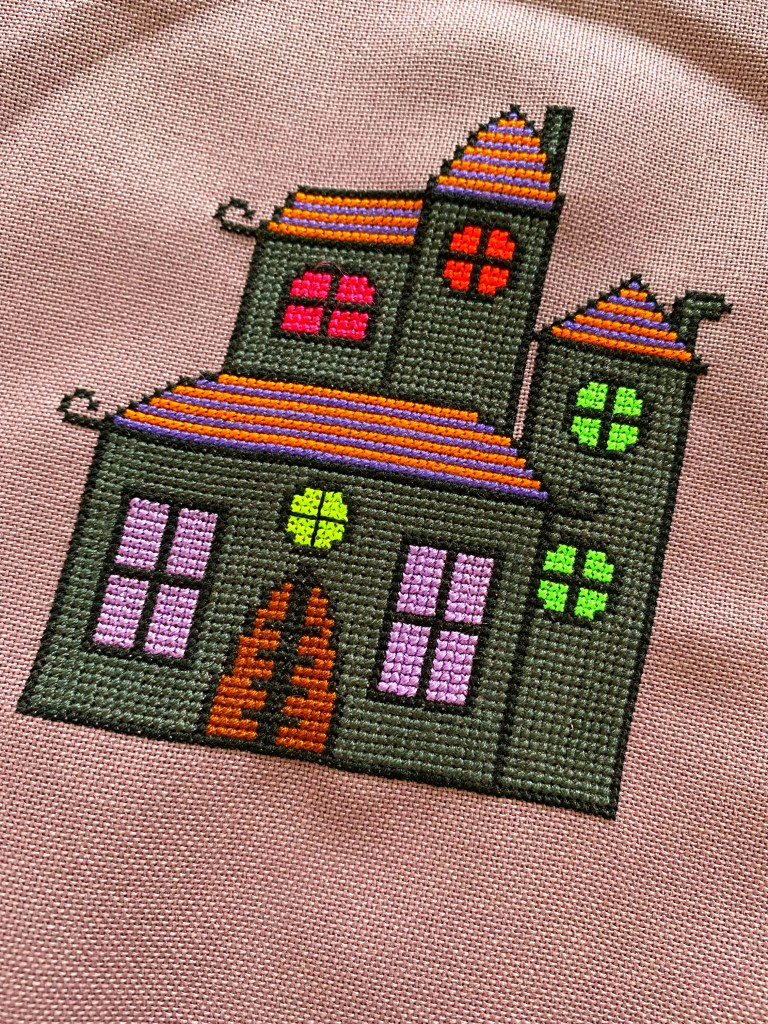 haunted house cross stitched onto purple evenweave fabric