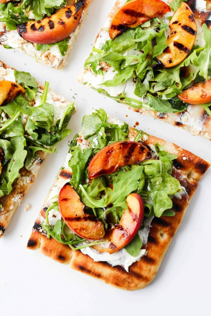 This Grilled Peach & Arugula Flatbread Pizza with warm goat cheese and balsamic drizzle is an easy and delicious vegetarian summer meal ready in 30 minutes.
