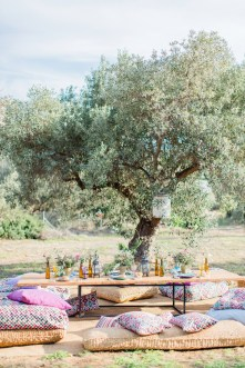 Wedding day garden reception set up with colorful plates, seasonal flowers and personalized place cards in Pyrgos Petreza Athens.