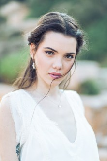 Bride in her wedding dress, hair and make-up and diamond jewellery posing for professional wedding day portraits in Athens.