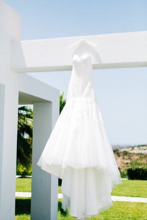 Image of a luxurious wedding gown hanging on a white walled villa with the background of green grass and blue sky in Crete.