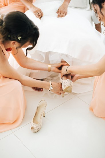 Professional wedding day of bridesmaids dressing up the bride and putting on her high heeled shoes.