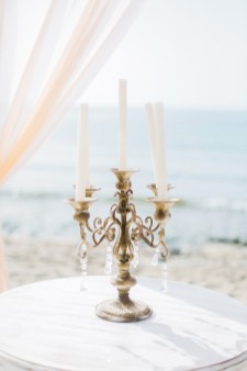 Professional wedding day detail image of a beach wedding ceremony set up decorated with flowers with the backdrop of sand and sea view in Crete.