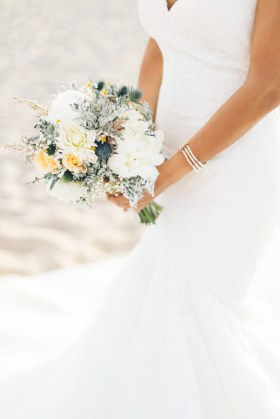 Professional Crete wedding photoshoot, closeup image of the bride holding her bouquet on the beach and posing for photographer.