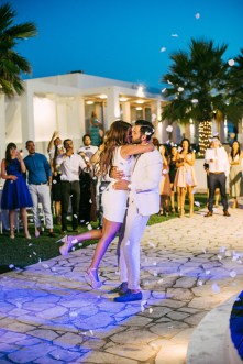 Wedding day reception portrait of bride and groom dancing their first dance and kissing, captured by the professional wedding photographer in Chania Crete.