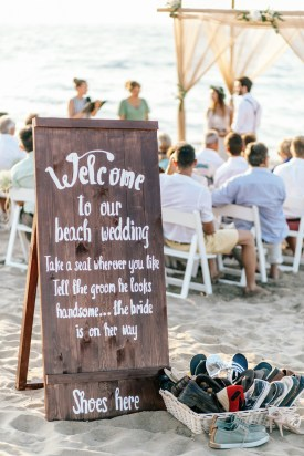 Welcome to our beach wedding sign with the bride and groom and teir guests in the background during a symbolic ceremony in Rethymno Crete.
