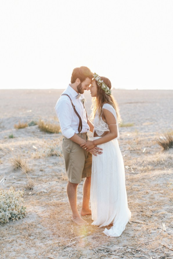 Wedding photograph of bride and groom posing for portraits for photographer standing on the beach with stunning sunset in the background.