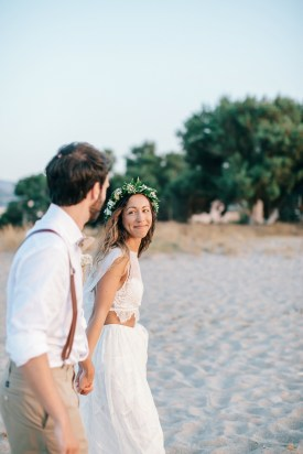 Professional image of bride and groom walking along a sandy beach in Crete after their beach wedding ceremony.