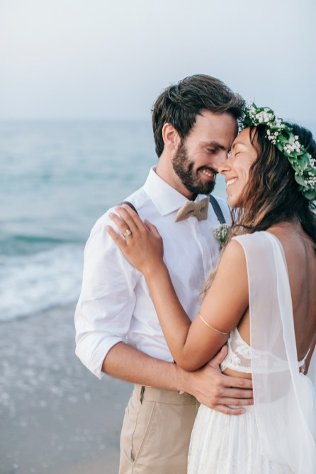 Professional image of bride and groom standing on the sea shore on a sandy beach in Crete after their beach wedding ceremony.