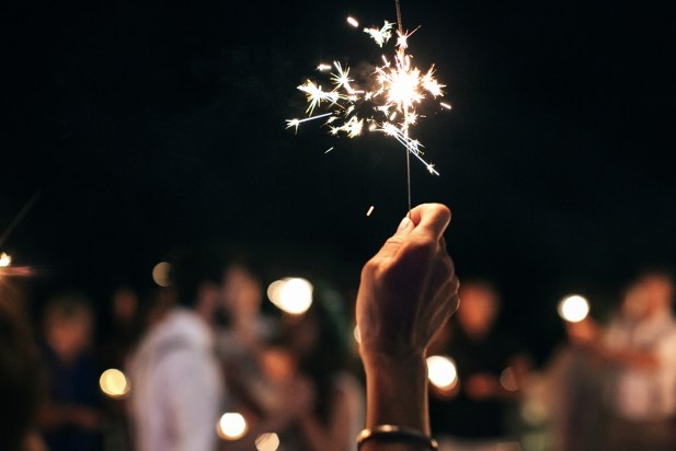 Closeup image of a guest's hand stretched out in the air and holding a sparkler with the wedding couple having their first dance in the background during the wedding reception.