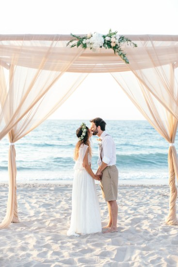 Newlyweds under boho wedding canopy on the beach in Crete island.