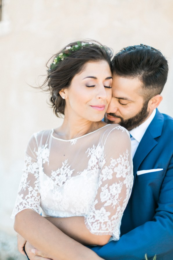 Professional wedding photosession in Crete, closeup portrait of bride and groom posing with Spinalonga island and sea view in the background.