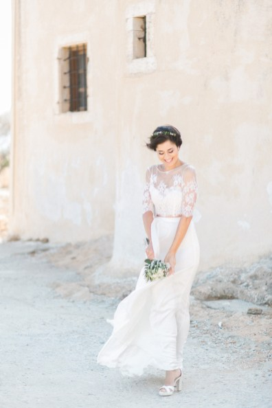 Professional wedding photoshoot in Crete, bride posing with Spinalonga island church and historical ruins in the background.