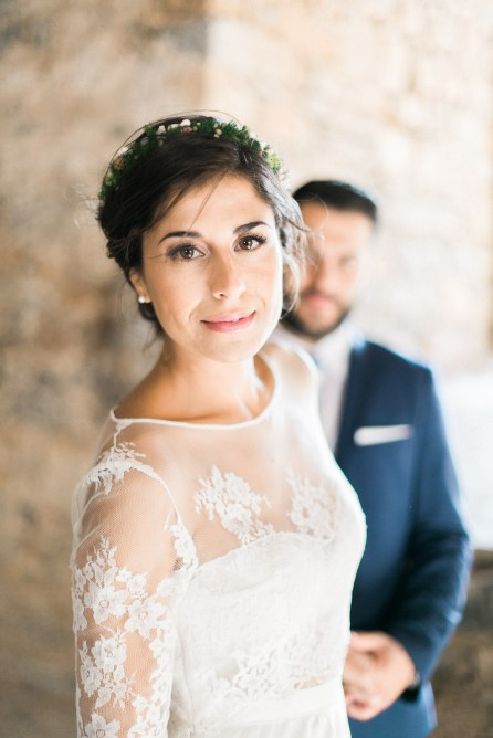 Professional wedding photoshoot in Crete, bride posing with groom with Spinalonga island historical ruins in the background.