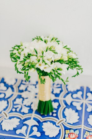 White fresia bridal bouquet styled by wedding photographer on blue mosaic floors in Caramel luxury hotel in Crete.