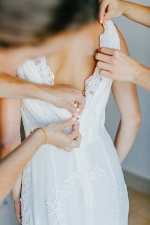 Bridesmaids dressing the bride on her wedding day, a close-up image of their hands fastening the bridal dress.