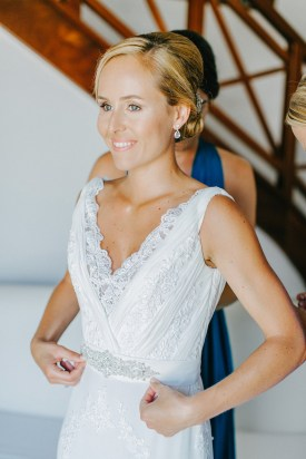 Beautiful bride getting ready for her wedding ceremony in Caramel hotel bridal suite, looking ahead and smiling.