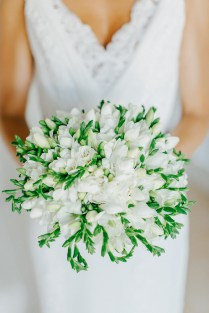 Professional image of a bridal bouquet being held by the bride with the background of white Pronovias dress.