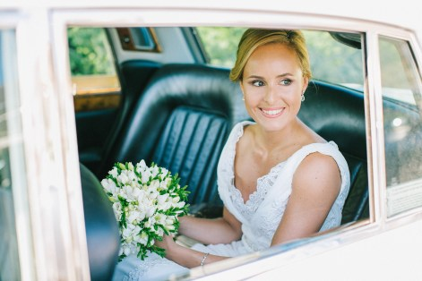 Bride looking out of the window of the luxury bridal car and smiling looking at her groom and guests.