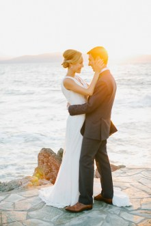 Beautiful sunset portrait of bride and groom posing together for their wedding photographer captured after the wedding ceremony in palm tree wedding estate in Rethymno Crete.