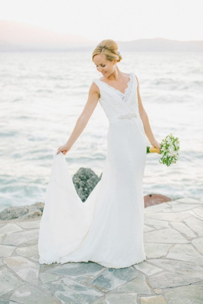 Professional portrait of bride posing for her wedding photographer wearing Pronovias bridal dress and holding flower bouquet captured after the wedding ceremony in palm tree wedding estate in Rethymno Crete with a sunset sea view background.